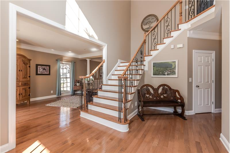 Gorgeous custom features include curved staircase, wrought iron balusters, hardwood floors and stair treads,
