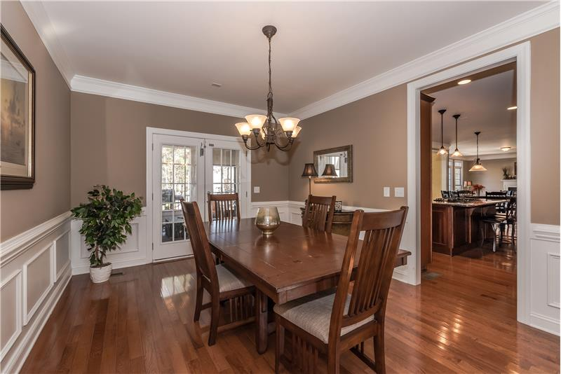 Dining room features gleaming hardwood floors, generous mill-work, double French doors leading to screened porch.