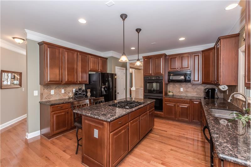 Lots of cabinets, granite counter-tops, large island with seating, tile back-splash, pantry.