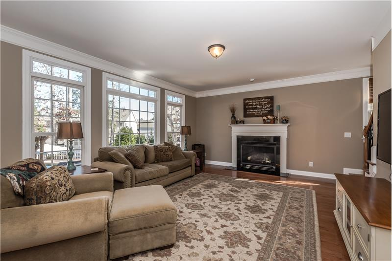 Bright and sunny family room with gas log fireplace, French-style windows with transom accents.