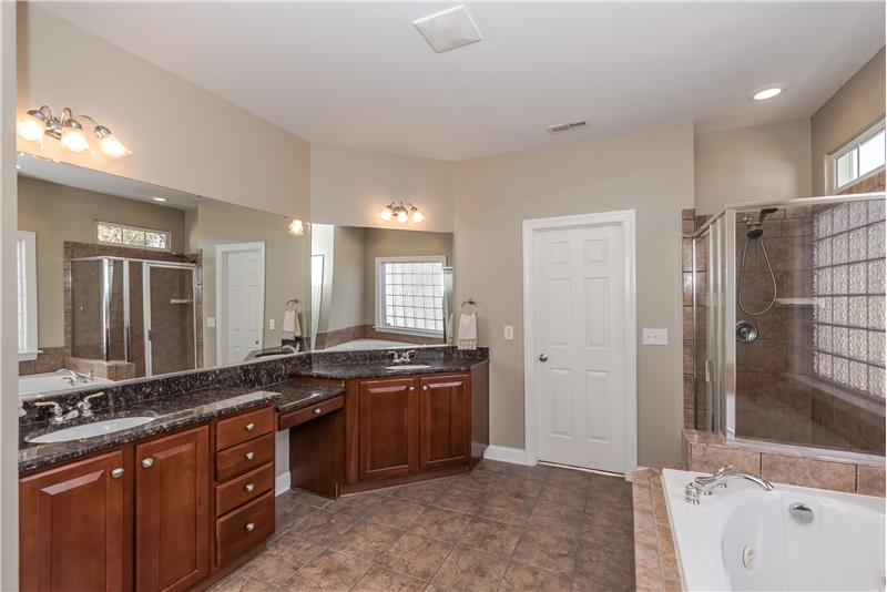 Spa-inspired master bathroom with expansive vanity, large shower, jetted soaking tub, tile surround, two walk-in closets.