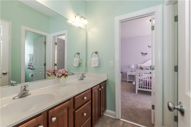 Jack & Jill bathroom with dual sink vanity shared by two of the secondary bedrooms.