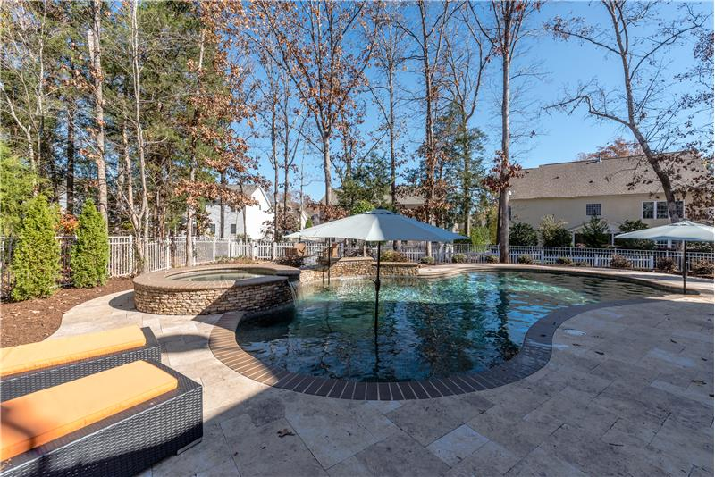 Hot tub/spa, waterfall, ozone chlorination are special features of the custom built pool.