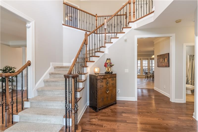 Soaring 2-story foyer with winding staircase with wrought iron balusters, gleaming hardwood floors