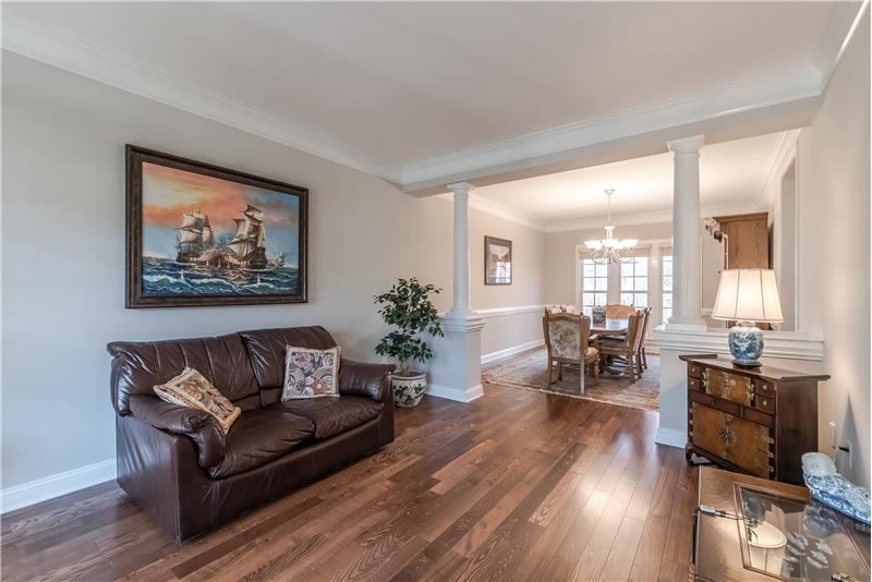 Living room features hardwood floors, crown molding, fresh paint. Open sight lines to dining room.