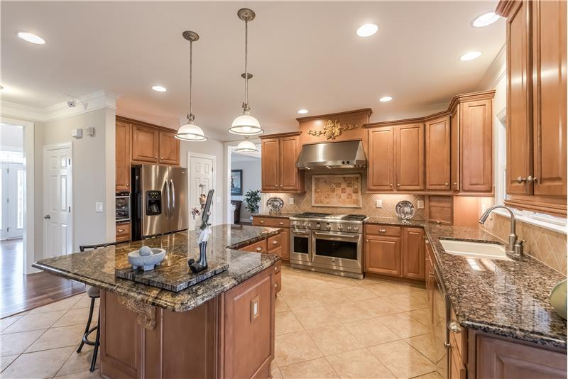 A kitchen any cook would love with island, custom cabinets, high-grade granite counters.