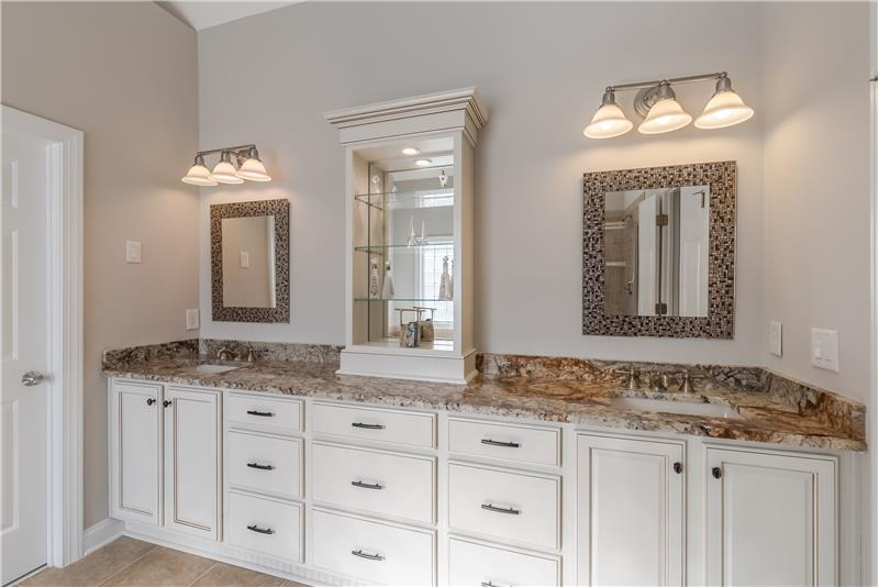 Master bath features raised, double sink vanity with granite counters, plentiful storage, designer mirrors.