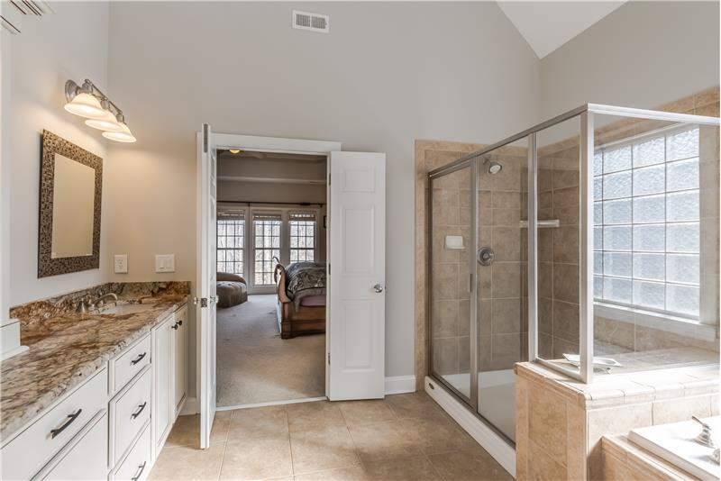 Spa-inspired master bath features tile floors, picture window, vaulted ceiling, private WC, large walk-in closet.