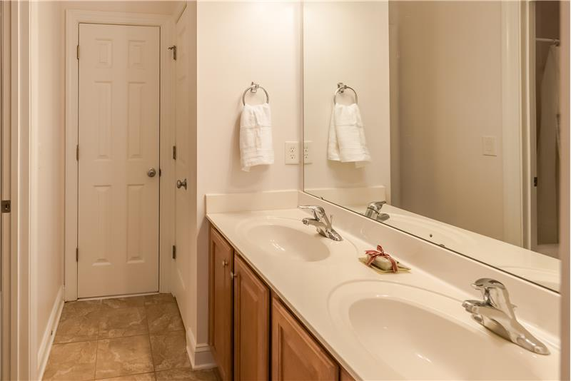 Jack & Jill bathroom shared by two of the second floor bedrooms with dual sink vanity, linen closet, separate tub/toilet area.