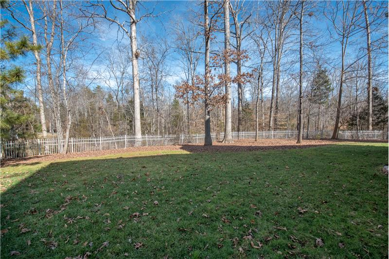 Wooded, fully fenced back yard provides privacy and plenty of room for a play set or even a pool.
