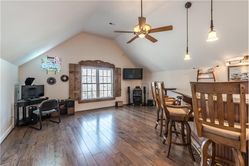 Large recreation room on the third floor features hand-scraped wood flooring, vaulted ceiling, custom window shutters.