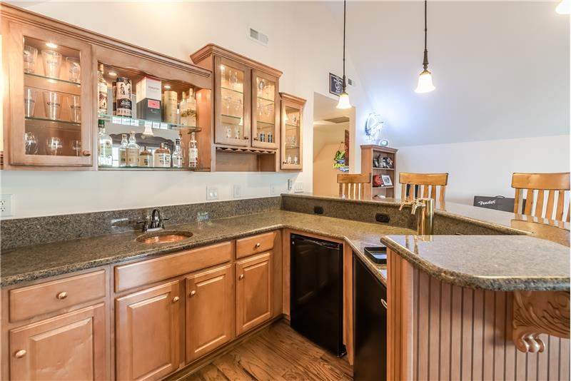 Bar area features copper sink, granite counters, fridge, built-in kegerator, custom cabinets.