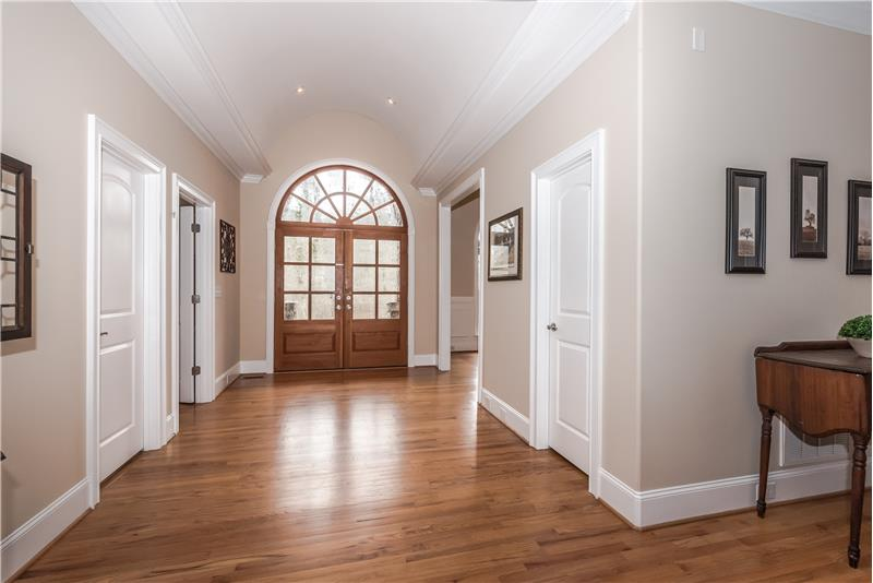 Dramatic foyer with barrel ceiling, gleaming hardwood floors, custom lighting, double door with etched glass, Palladian window.