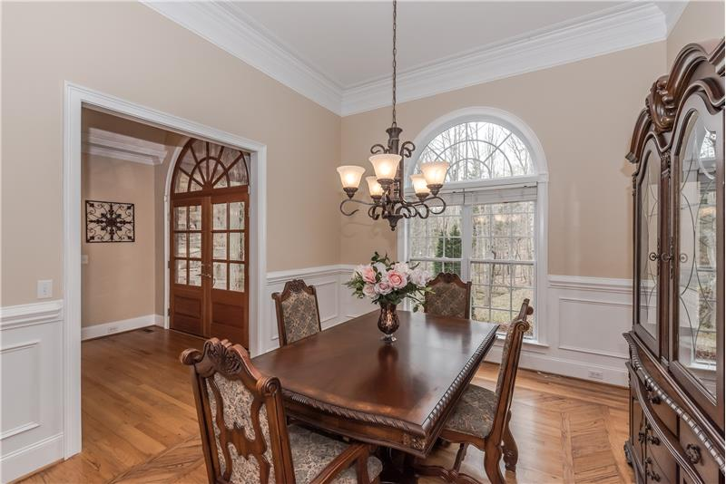 Elegant formal dining room with hardwood floors, Palladian window, generous millwork.