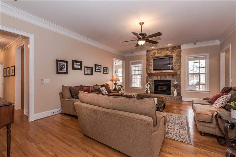 Over-sized great room features a large fireplace with stone surround and hearth and a wood mantel as its focal point.