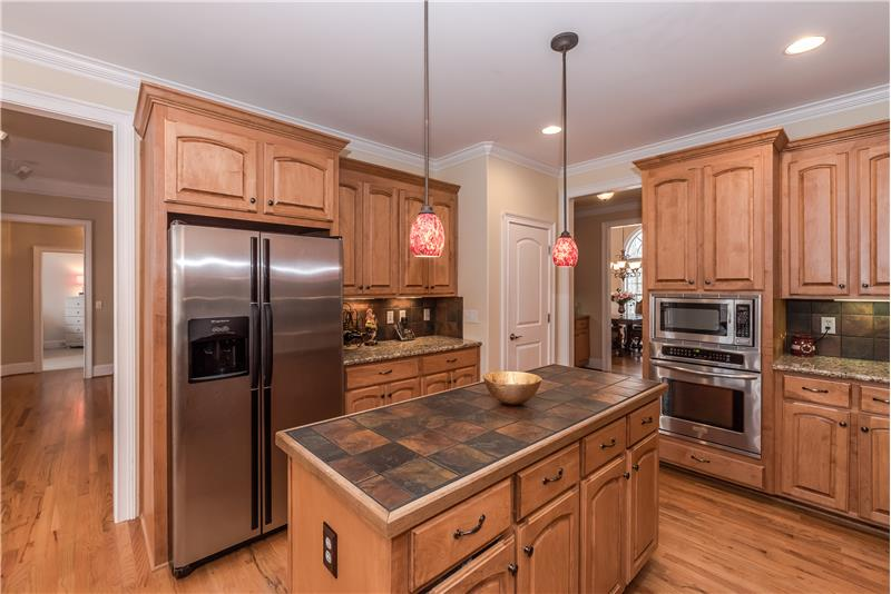 A full complement of stainless steel appliances includes a wall oven and microwave, dishwasher, side-by-side fridge.