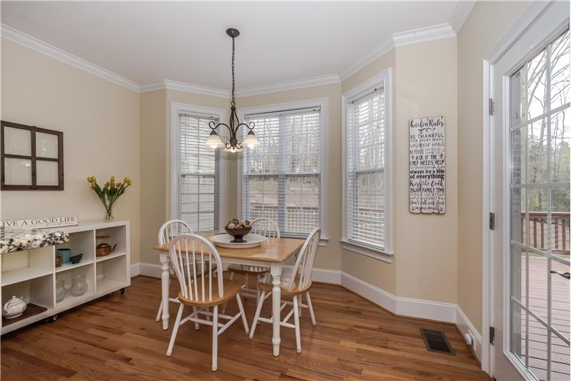 Sunny breakfast area adjacent to the kitchen and nestled in a bay window has hardwood floors, crown molding, wooded views.