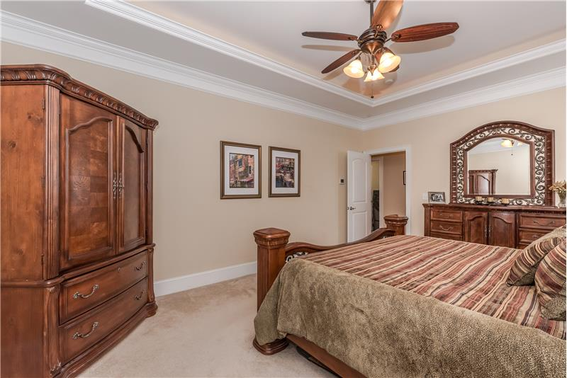 Master bedroom features a trey ceiling with cove lighting, crown molding.