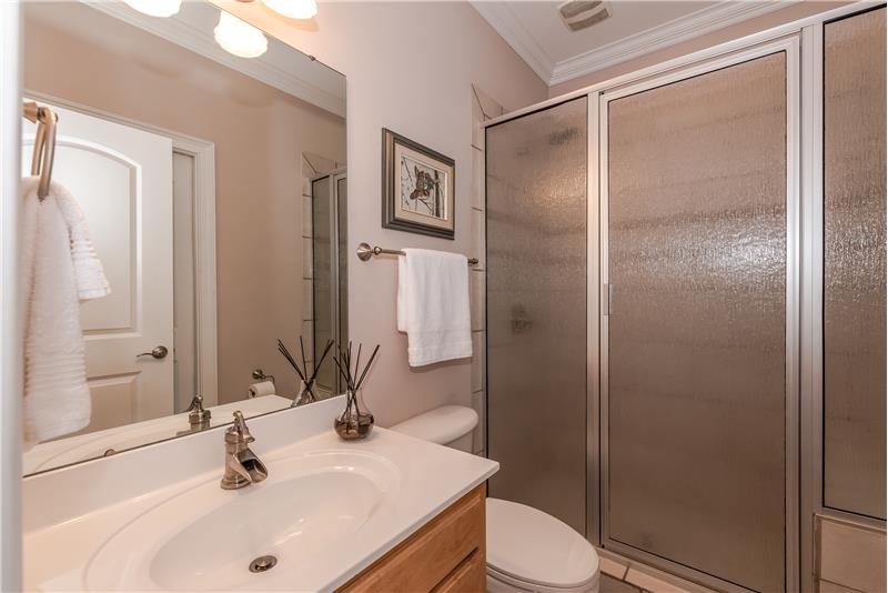 Guest bathroom accessible from both the foyer and the adjacent bedroom. Tile flooring and surround; crown molding.
