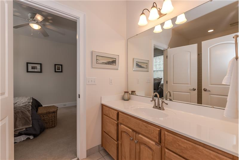 Jack & Jill bathroom shared by two of the secondary bedrooms in the home features expansive vanity, tile floors.