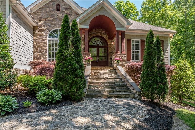 A front entrance with barrel ceiling that is sure to impress with it's stone walkway and stairs and stately entrance door.