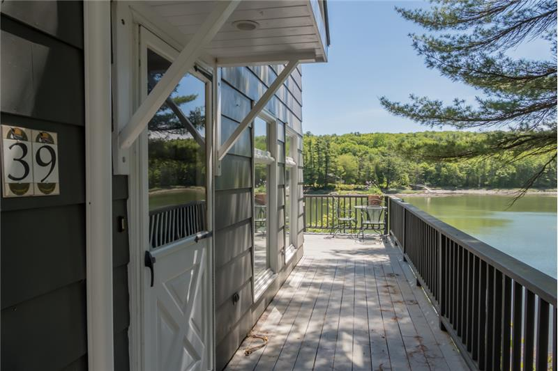 One of the first things you'll notice is this glorious deck that wraps around the house and hangs over the water.
